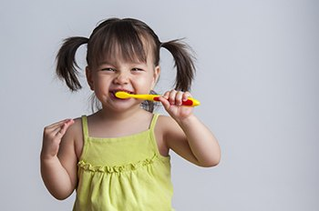 Little girl brushing her teeth to avoid pediatric dental emergency