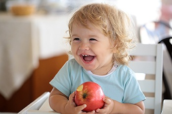 Child eating apple to prevent pediatric dental emergency