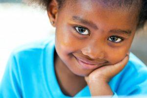 smiling child holding face blue shirt