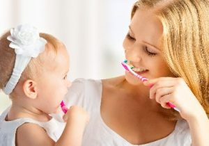 Mother and her child brushing their teeth