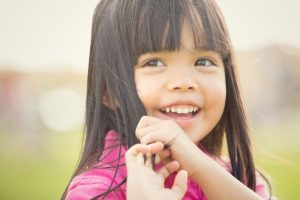 young girl smiling rubbing hair