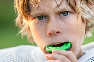 young boy blonde hair green mouthguard