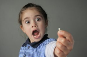 Girl holding tooth shocked at losing baby teeth