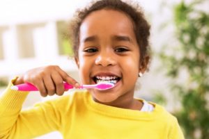 smiling little girl brushing her teeth for better oral health