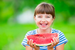 Smiling girl with watermelon and good children's oral health