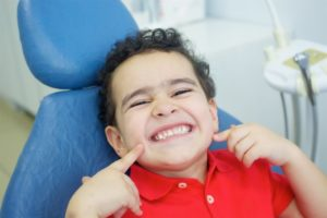 Smiling boy points to his new dental sealants for children